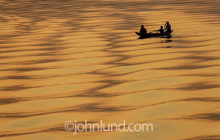 This photo of a sunset on the Irrawaddy river in Myanmar, featuring several men in their small boat silhouetted against the orange waters evokes feelings of solitude, tranquilty and the rewards of exotic travel to far away places.