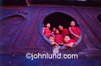 Young monks in Myanmar Gathered together in a group looking out through a round window. Buddhism is the predominant spiritual belief in Burma