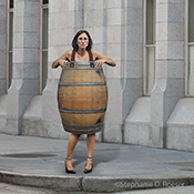 A businesswoman stands on an urban street corner wearing only a barrel in a stock photo about challenge, financial adversity, and bankruptcy.