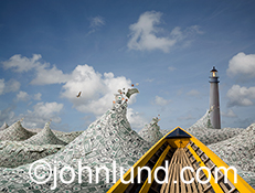 A yellow boat navigates through waves of money towards a distant lighthouse in an image about financial planning, investing, retirement and other money issues.