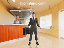A funny sales guy stands at the ready in a corporate lobby in front of a dubious looking receptionist in this parody photo of an over confident salesman. His suit is too small, his expression too arrogant and his chances of success slim to none!