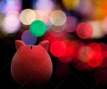 A piggy bank looks out a bright city lights at night in a stock photo about temptation for spending.