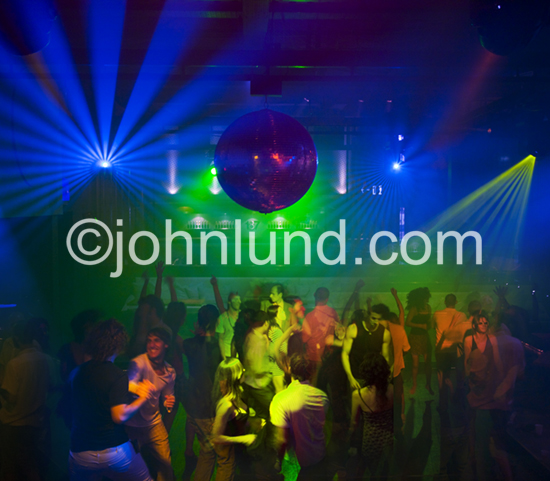 Classic photo of a night club scene with energy, excitement, dancing people, colored lights, disco ball and smoky atmosphere.