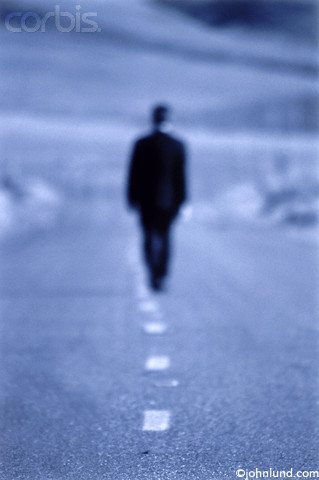 Picture of a man walking alone down a desolate and empty road in an ...