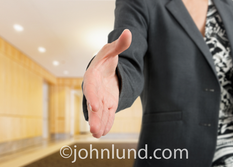 A woman executive offers her hand for a shake to seal the deal in a corporate highe end office setting.