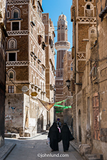 Photograph of a street in the old city of Saana with Abaya clad women. In the background a minaret from one of the many mosques rises into the blue sky.