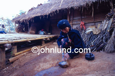 Picture of a Hmong Tribal Woman sharpening her knife on a stone in her village in Burma. In her mouth is a traditional Burmese pipe.