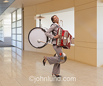 A successful one woman band is seen in this stock photo featuring a smiling African American business woman, outfitted with musical instruments, and standing in a business environment.