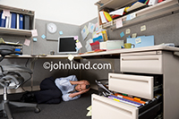 An overwhelmed businessman hides beneath his cubicle desk with his hands over his ears and his eyes tightly shut.