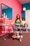 An attractive young woman is sitting in a hair dresser's chair in a hair salon.  Woman in the background under a hair dryer. Bright pink wall in the background.  Pink shoes.