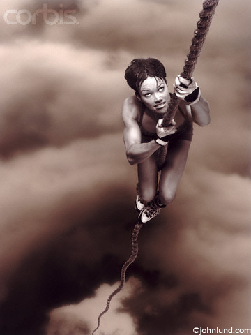 Photo of a woman climbing a long rope with a look of extreme determination.  The woman is so far up the rope that the clouds are below her as though she is climbing up through a hole in the clouds.