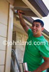 Hispanic man making a home improvement by painting the exterior of his house. Happy man in a green shirt painting his house with a paint brush and a can of paint.