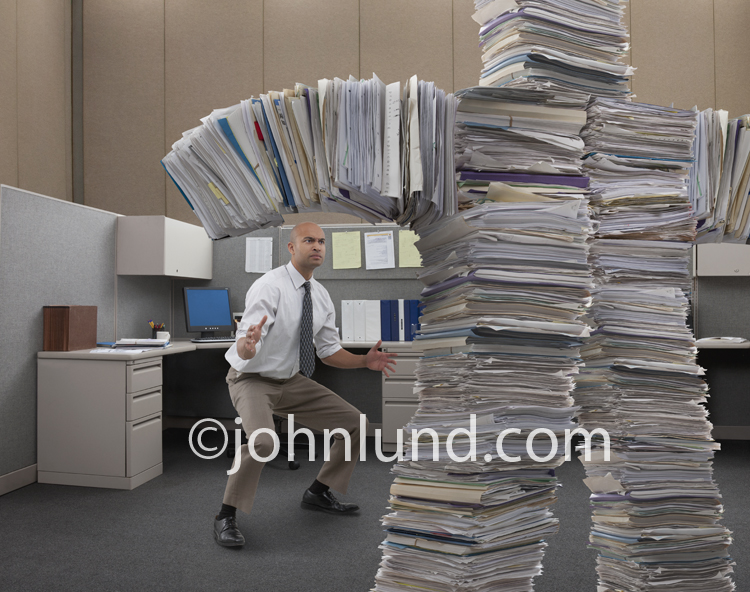 A businessman prepares to wrestle with a paper work monster in an image about work place pressure, excessive regulations and paper work, and business challenges.