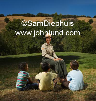 Group of young children gathered around a woman park ranger and listening to her stories. She is educating the children about nature and national parks. The ranger is happy and smiling. Picture of kids listening to stories.