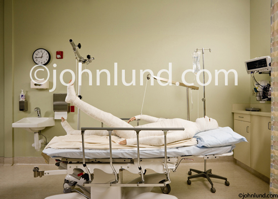 Picture of a patient laying in bed in a recovery room in a body cast, traction and with his head bandaged. Iconic photo of a full body cast.