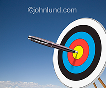 A pen hits the bullseye on a target in this stock photo illustrating the power of the written word and the importance of on target and well-targeted writing.