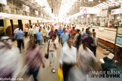 Picture of a rushing crowd in a busy Mumbai train station. Some motion blur on people close to the camera. Trains in Mumbai.