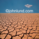 Stock picture of an expanse of dry cracked earth with a single cloud overhead in the distance showing ecological problems and global warming.