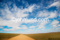 Stock shot of a dirt road stretching to the horizon on the vast plateau of Mongolia: Adventure Travel and vacations. Long lonely road pics.