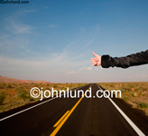 Stock photo of a elegantly clad arm hitch hiking on a long deserted road leading into the distance across the desert landscape. Pictures of hitch hikers.