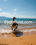 Stock photo of a goose wading into the lake water from a sandy shore. In the distance is a mountain range. Beautiful clear blue water and a mostly blue,partly cloudy sky. A beautiful summer day for a swim.