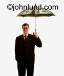 A man holds an umbrella made from a dollar over his head in this stock photo aimed at business and financial issues.
