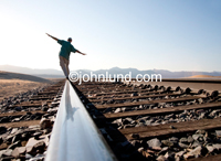 Stock shot of a man walking on the railroad tracks and trying to maintain his balance on his journey of self discovery.