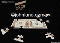 Stock photo or  image of a dollar bill as a jigsaw puzzle - great concept photo for financial uses. Puzzle is mostly complete with a few missing pieces which are close by.  Image is on black background.