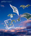 Stock photo of a window frame in the sky with winged money flying through and around it. Dark blue sky with redish clouds. Could represent wasted money.
