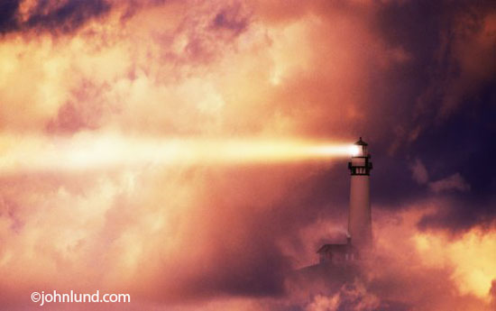A lighthouse casts its beam of light through the fog at sunset. This is Pigeon Point Lighthouse off the Northern California coast.