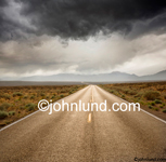 Stock shot of a long straight road stretching to the horizon while dark clouds drift overhead and skies clear in the distance.