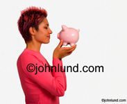 Mixed race woman looking at piggy bank she is holding in her hands. The short red haired woman holding the piggy bank almost nose to nose with the pig.  She is wearing a bright red or pink blouse.