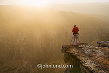 Luka Esenko stands on a rock outcropping as he photographs a stunning sunrise over a deep gorge on Socotra Island in the Homhil Protected Area.