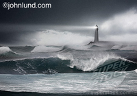A lighthouse casts its beam of light across the storm seas in a concept stock picture of a lighthouse at dusk.