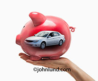 In this photo a hand holds up a Piggy Bank with a brand new car showing within in a photographic metaphor for car financing, new car purchases, and automobile loans.