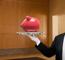 A piggy bank is presented on a silver tray by a butler in a stock photo about service in the banking, savings, and investment world.