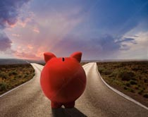 A piggy bank faces a fork in the road in a stock photo about investment and saving choice.