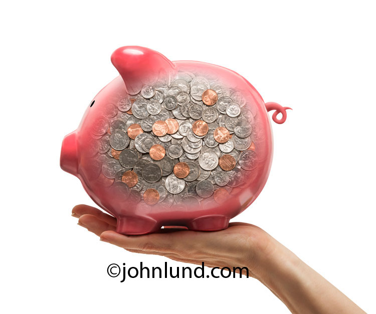 The piggy bank in this photo is filled to the brim with coins that are visible through the semi-transparent sides of the pink ceramic piggy in an image about savings and investment.