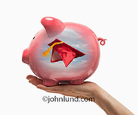 A Piggy Bank with a mortar board college graduation cap inside is held up by a hand in an image about college funds, student loans, and education finance.