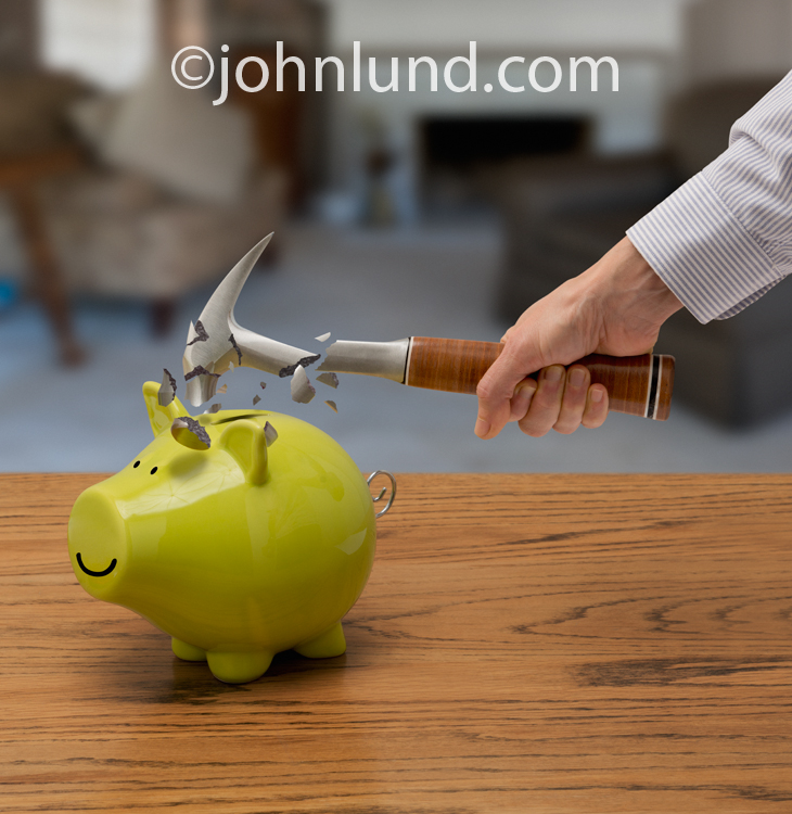 In this photo a green piggy bank survives a hammer strike and it is the hammer that shatters into pieces symbolizing strong savings strategies.