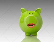 A green piggy bank wears lipstick in a stock photo that conveys the idea of deceptive investment practices particularly when it comes to environmentally sensitive investments.