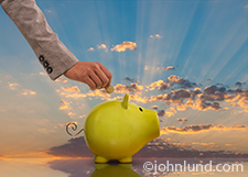 A woman's arm reaches into the frame as she is about to place a coin inside a green piggy bank against a backdrop of a dramatic sunrise in an image about savings, investment and new beginnings.