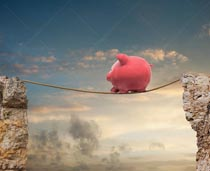 A piggy bank traverses a tightrope between two cliffs in this stock photo about savings, investment and finance.