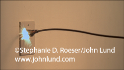 A super slow motion video of a power cord entering the frame and plugging into a wall socket with a flash of sparks.