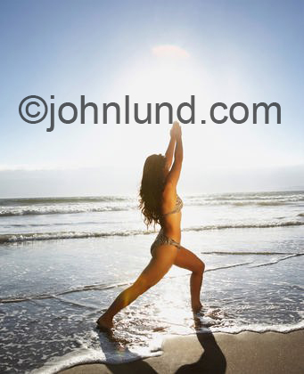 Image of a woman in a bikini swim suit practicing yoga positions on the sandy beach with the waves lapping at her feet.