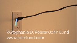 A black power cord is pulled from a wall socket in a super slow motion video. Sparks fly as the plug is pulled after which the cord begins to spin on its way out of the frame in a video about concepts such a pulling the plug, termination and boundaries.