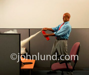 Picture of a business man using a fire extinguisher to put out a fire in his office cubicle.  Man in a suit putting out fires in the office. Bald black man using a fire extinguisher.