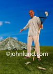 Raking in the money is what this image depicts. A smiling man is holding a rake in one hand and gesturing with the other to a large pile of money he has raked into a pile. Picture of pile of money.