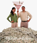 Happy hispanic couple standing in a huge pile of money, dollar bills, US currency, and they are both holding onto an old fashioned rake with a few bills caught in the tines.  They are smiling and happy. Money pic.