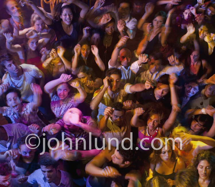 A high angle and colorful view of an packed and enthusiastic crowd disco dancing in a rave or nightclub.